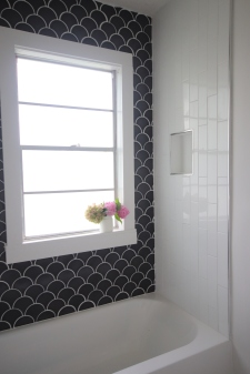 tub surround using two different tiles. The accent tile is a dark fan-shaped tile and the main tile is a long white subway tile layed vertically.