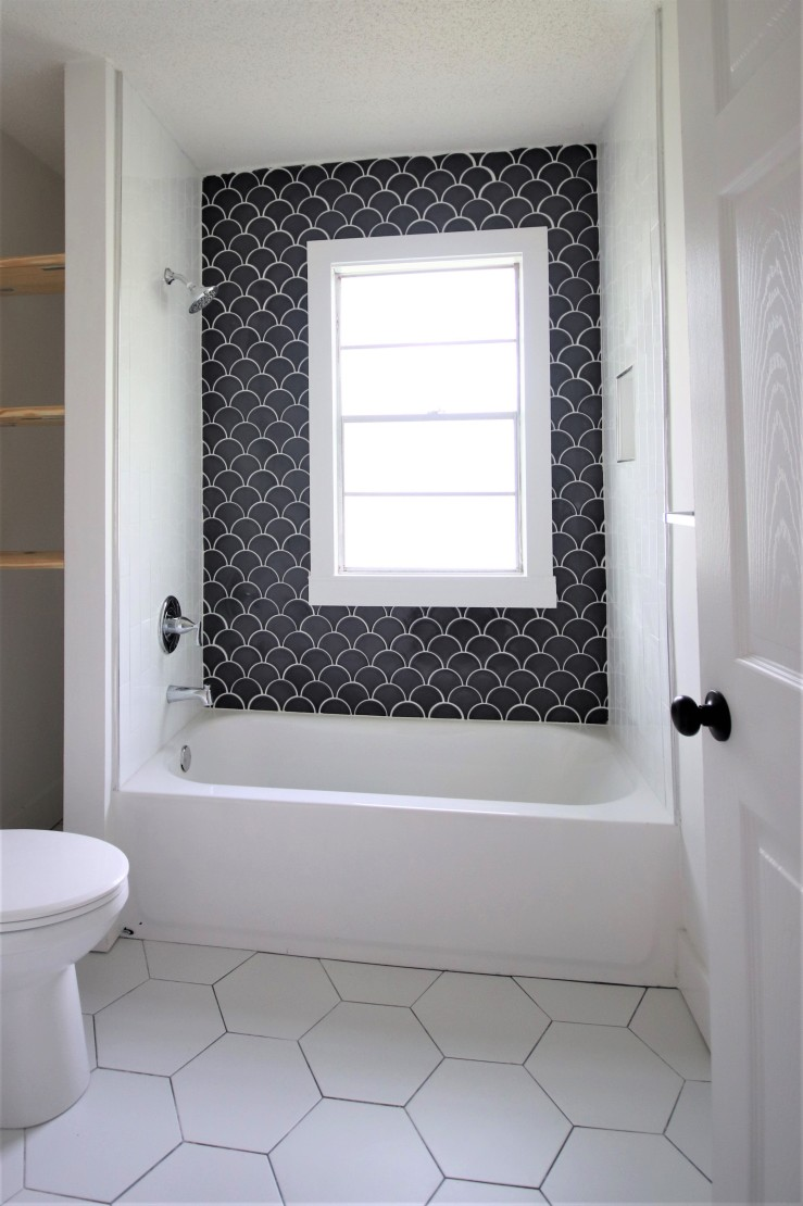 Bathroom with large white hexagon floor tile and tub surround with dark fan-shaped tile