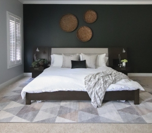 wood and upholstered king size bed with integrated hightstands and white linens in front of a dark green accent wall